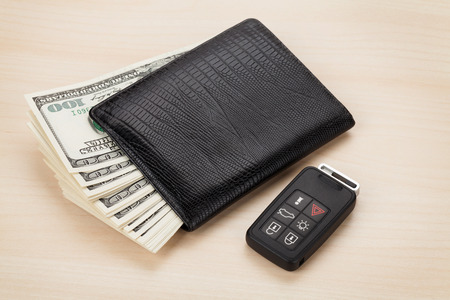 Money cash wallet and car remote key on wooden table photo