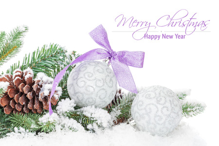 Christmas baubles and purple ribbon with snow fir tree. Isolated on white background with copy space photo