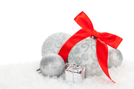Christmas baubles and red ribbon over snow with copy space photo