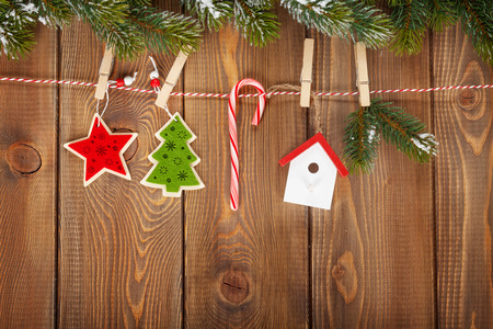 Snow fir tree and christmas decor on rope over rustic wooden board with copy space photo