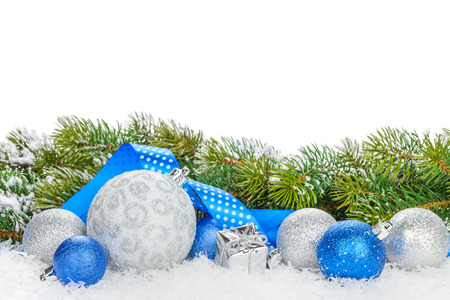 Christmas baubles and blue ribbon with snow fir tree. Isolated on white background with copy space Stock Photo