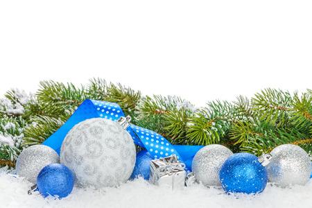 spar: Kerstballen en blauw lint met sneeuw spar. Geïsoleerd op een witte achtergrond met een kopie ruimte