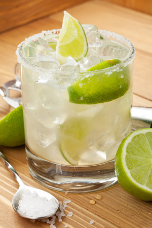 margarita: Classic margarita cocktail with salty rim on wooden table with limes and drink utensils Stock Photo
