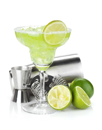 margaritas: Classic margarita cocktail with salty rim, limes and drink utensils. Isolated on white background Stock Photo