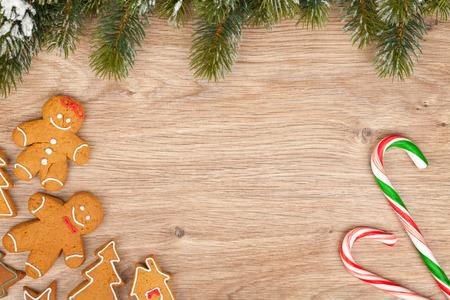 casita de dulces: �rbol de abeto de Navidad y galletas de jengibre en tabla de madera
