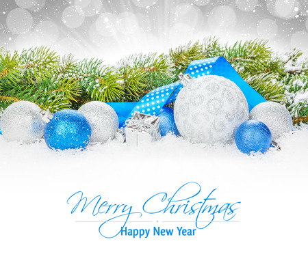 Christmas baubles and blue ribbon with snow fir tree over bokeh background with copy space photo