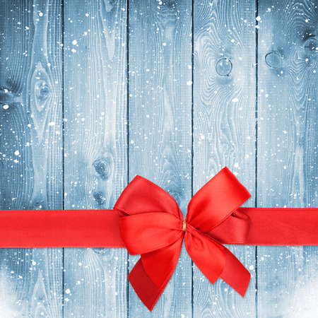 Red ribbon with bow over christmas snow wood background with copy space