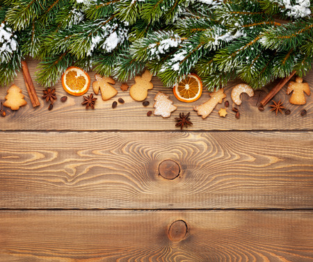 Christmas wooden background with snow fir tree, spices, gingerbread cookies. View from above with copy space