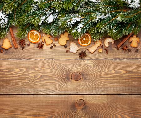 Kerst houten achtergrond met sneeuw dennenboom, specerijen, peperkoek cookies. Zicht van bovenaf met een kopie ruimte Stockfoto