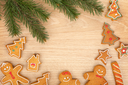 Christmas fir tree and gingerbread cookies on wooden board photo
