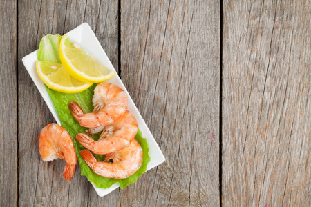 prepared shrimp: Cooked shrimps with lemon and salad leaves. View from above on wooden table with copy space Stock Photo