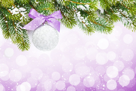 Christmas colorful decor and snow fir tree over bokeh background with copy space