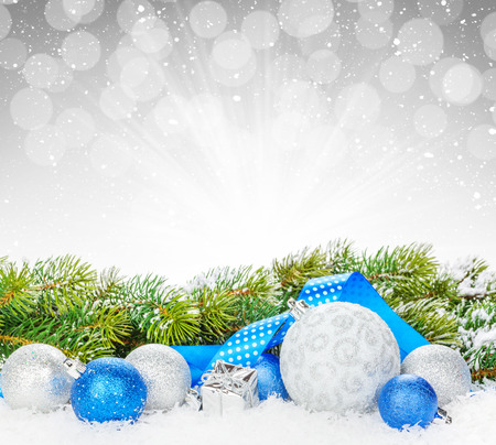 winter decorations: Christmas baubles and blue ribbon with snow fir tree over bokeh background with copy space