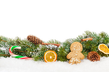 Christmas food and decor over snow fir tree. Isolated on white background with copy space photo
