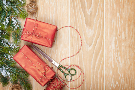 christmas wrapping: Christmas presents wrapping and snow fir tree over wooden table background with copy space