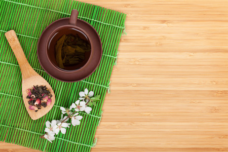 Japanese green tea and sakura branch over mat and bamboo table with copy space