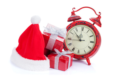 Christmas clock, gift boxes and santa hat. Isolated on white background photo
