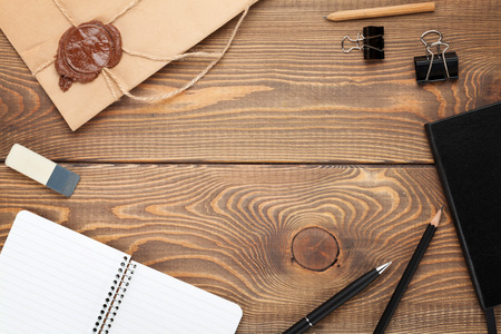 Office table with notepad, vintage envelope and supplies. View from above with copy space photo