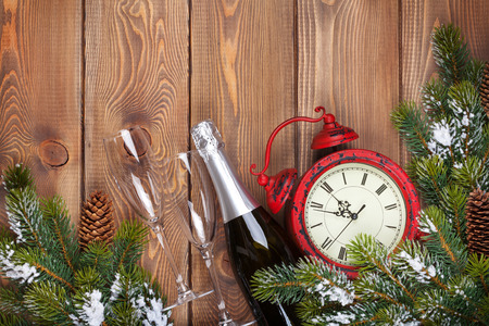 Christmas wooden background with clock, champagne, snow fir tree and copy space photo