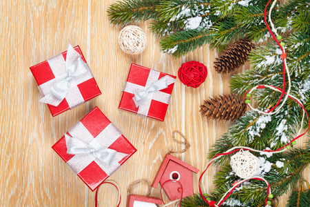 Christmas wooden background with snow fir tree, decor and gift boxes photo