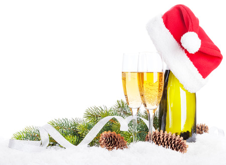 Champagne, christmas decor and santa hat over snow and fir tree with copy space photo