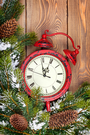 Christmas clock over wooden background with snow fir tree closeup photo