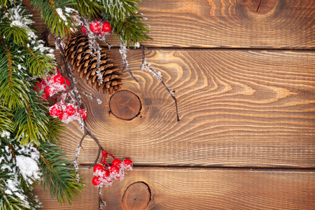 pine fruit: Christmas wooden background with snow fir tree and decor with copy space