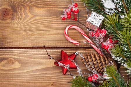 Christmas wooden background with snow fir tree and decor with copy space photo