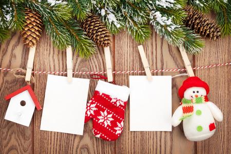 Sneeuw spar, fotolijsten en kerst decor op touw over rustieke houten bord met een kopie ruimte