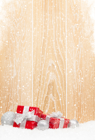 red snowflake background: Christmas gift boxes and decor with snow wooden wall with copy space