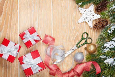 Christmas presents wrapping and snow fir tree over wooden table background with copy space photo