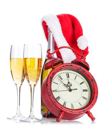 Two champagne glasses, santa hat, bottle and clock. Isolated on white background photo
