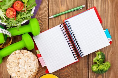 salud y deporte: Dumbells, cinta m�trica, la comida sana y el bloc de notas para el espacio de la copia. Fitness y salud. Aislado en el fondo blanco