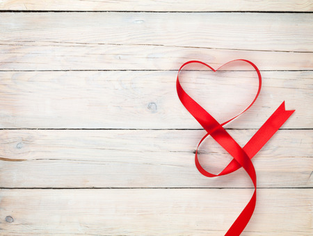 Valentines day background with heart shaped ribbon over white wooden table background Stock fotó