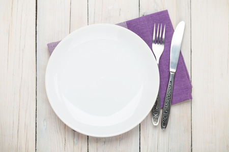 plate setting: Empty plate and silverware over white wooden table background. View from above