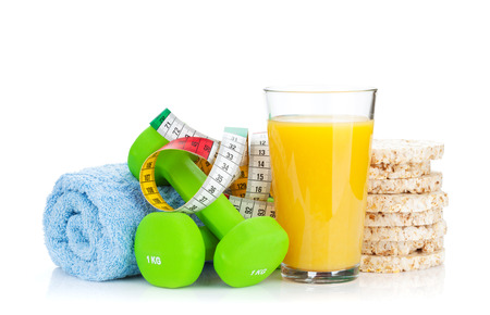 Two green dumbells, tape measure and healthy food. Fitness and health. Isolated on white background photo