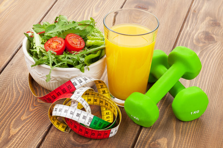 Dumbells, tape measure and healthy food over wooden table. Fitness and health photo