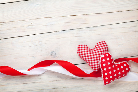 Valentines day background with toy hearts and ribbons over white wooden table background photo