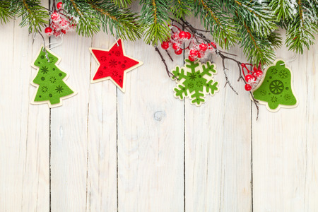 Christmas wooden background with fir tree and decor. View from above with paper for copy space photo