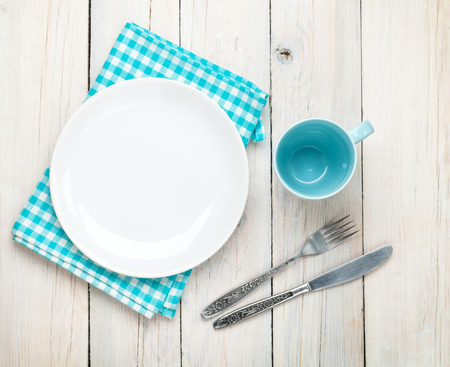 blue metal: Empty plate, cup and silverware over white wooden table background. View from above