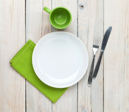 Empty plate, cup and silverware over white wooden table background. View from above