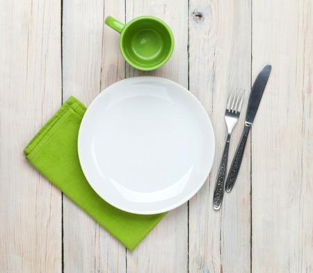 Plato vacío, taza y cubiertos de madera sobre blanco fondo de la tabla. Vista desde arriba Foto de archivo - 33976255