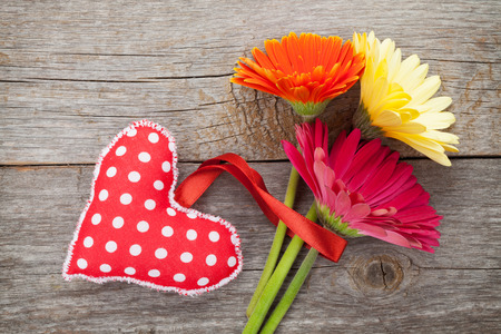 Colorful gerbera flowers and Valentines day heart toy. On wooden background with copy space photo