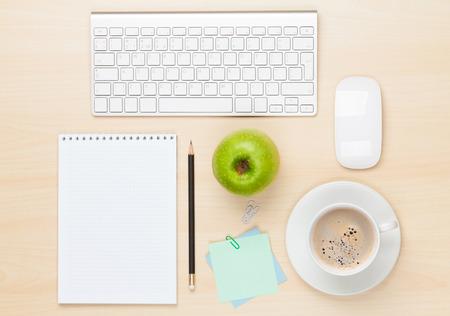 Kancelářský stůl s poznámkový blok, počítač a šálek kávy. Pohled shora