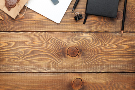psací stůl: Kancelářský stůl s poznámkový blok, vintage obálky a zásoby. Pohled shora s kopií vesmíru