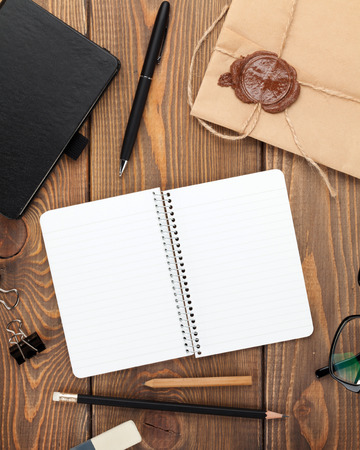 Office table with notepad, vintage envelope and supplies. View from above with copy space Stock Photo