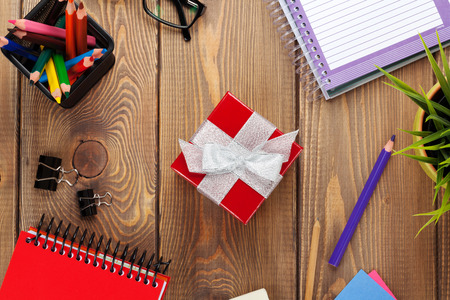 flower box: Red gift box and office supplies over office table. View from above Stock Photo