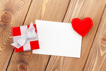 Photo frame or greeting card with gift box and toy heart over wooden table background photo