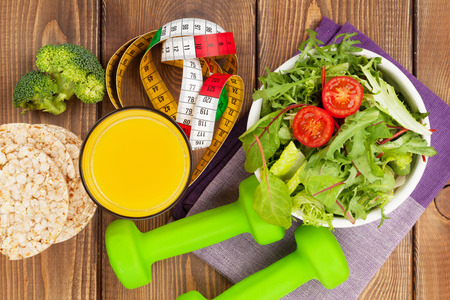 health: Dumbells, tape measure and healthy food over wooden table. Fitness and health