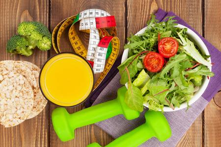 Hantlar, måttband och hälsosam mat över träbord. Fitness och hälsa